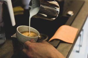 Šálek prémiové kávy s mlékem připravovaný v pražírně kávy