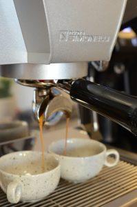 Profesionální kávovar Nuova Simonelli ve stříbrném provedení připravuje lázeňskou kávu