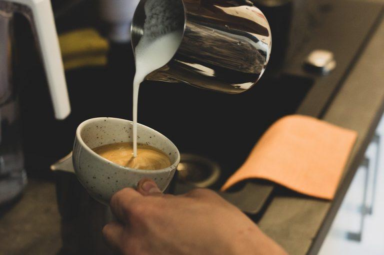 příprava kávy cappuccino nalíváním našlehaného mléka do espressa