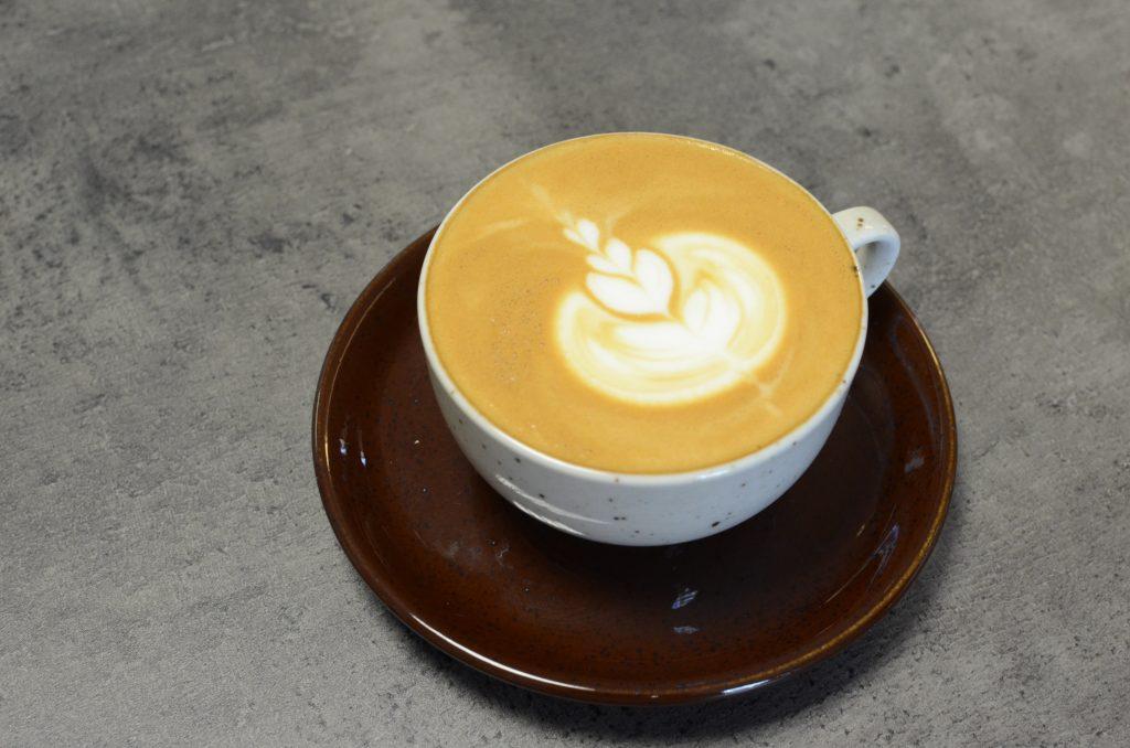 Šálek kávy Caffe Latte zdobené obrázkem technikou latte art
