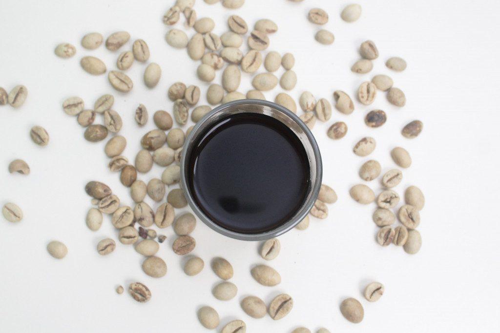 sklenice kávy a zrna zelené kávy