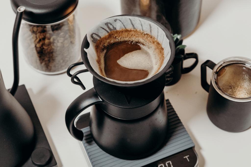 Příprava kávy v černém kovovém dripperu Hario V60 s baristickým příslušenstvím fellow, acaia váhou a miir plecháčkem na kávu