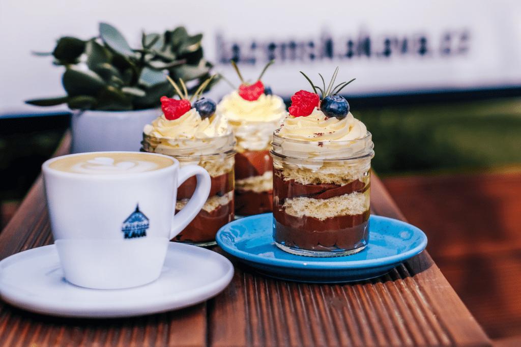 šálek Lázeňské kávy v kavárně s dezertem