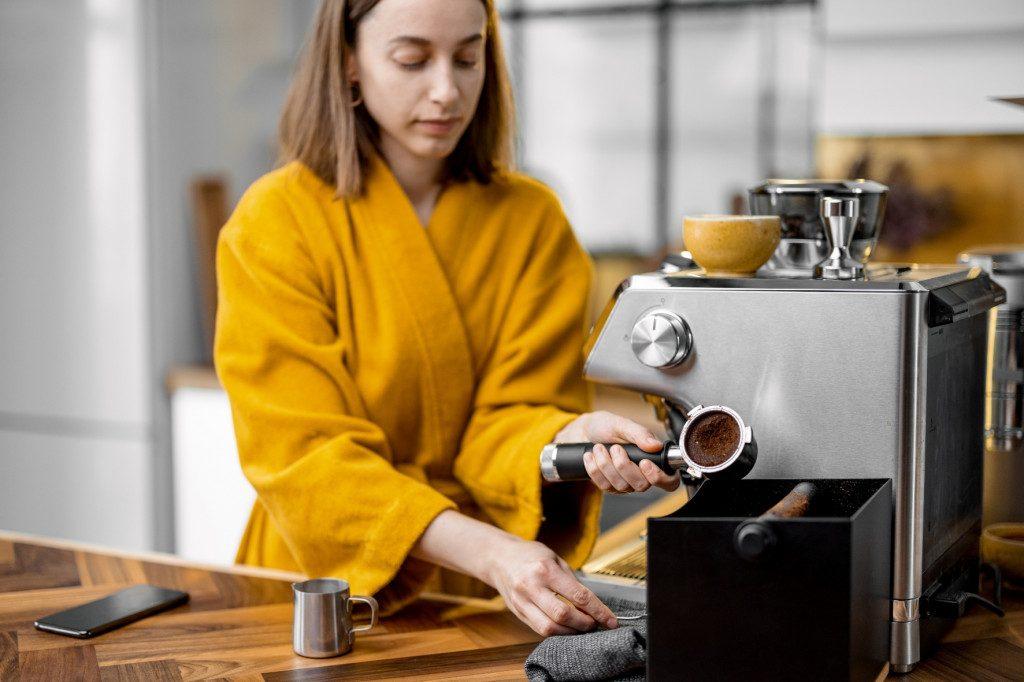 ranní příprava espressa v kuchyni na domácím pákovém kávovaru