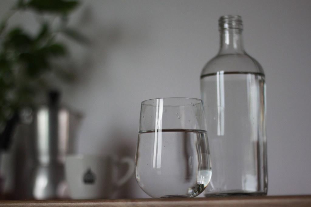 sklenice a láhev s vodou přichystané pro správnou přípravu kávy