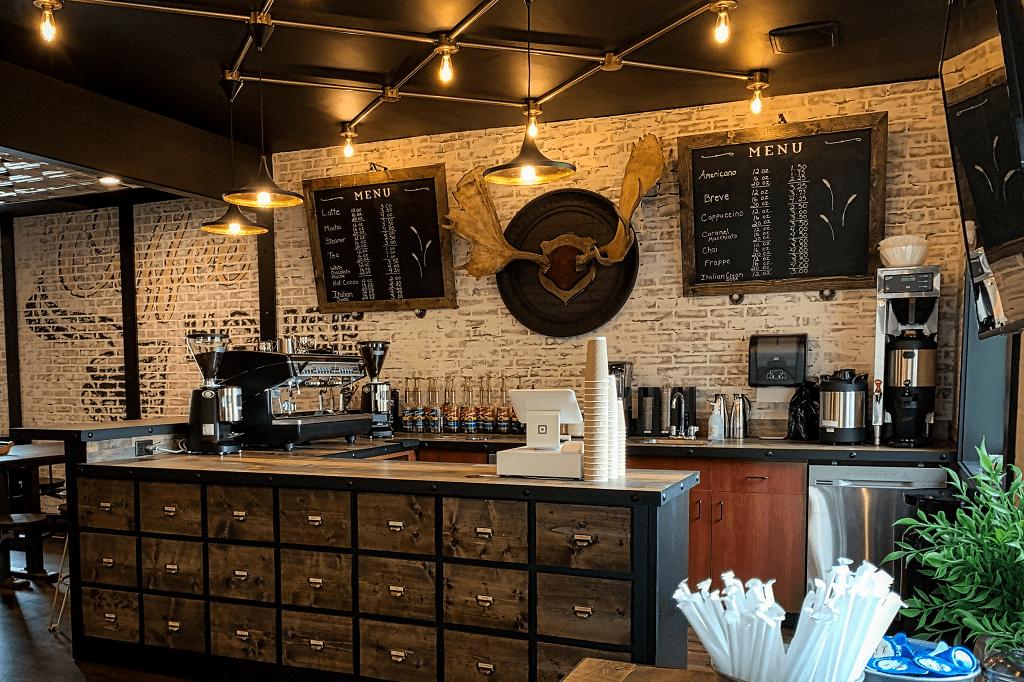 pohled na dřevěný bar v kavárně s kávovarem, kasou a kávovým příslušenstvím