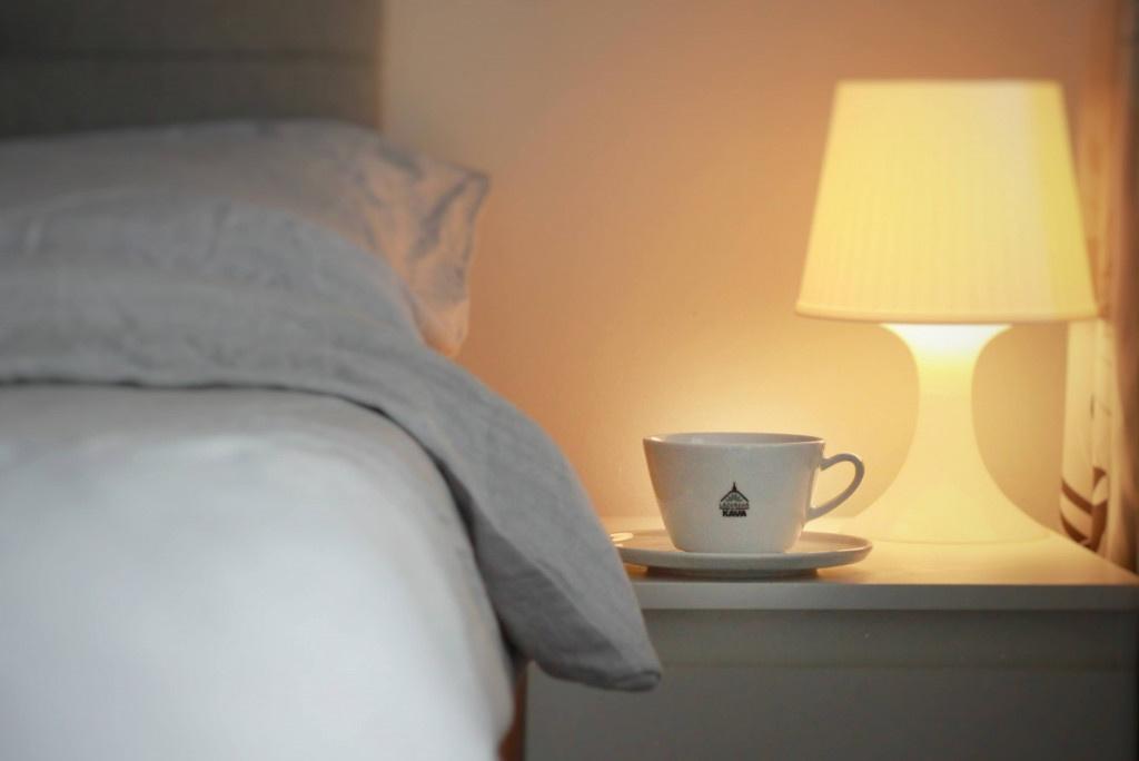 bílý šálek kávy Lázeňská káva na nočním stolku u postele