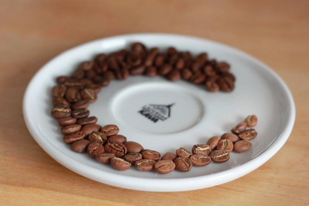 světle pražená zrnka kávy na podšálku pražírny Lázeňská káva