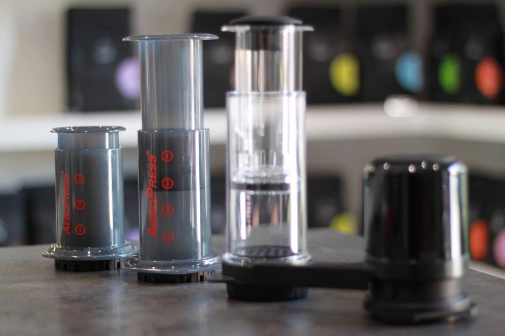 šedý plastový Aeropress a Aeropress Go, čirý plastový Delter Coffee Press a černý Twist Press