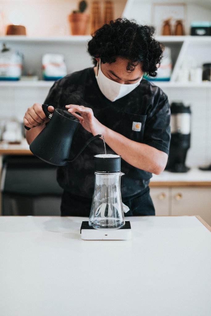 barista s rouškou přes ústa připravuje filtrovanou kávu