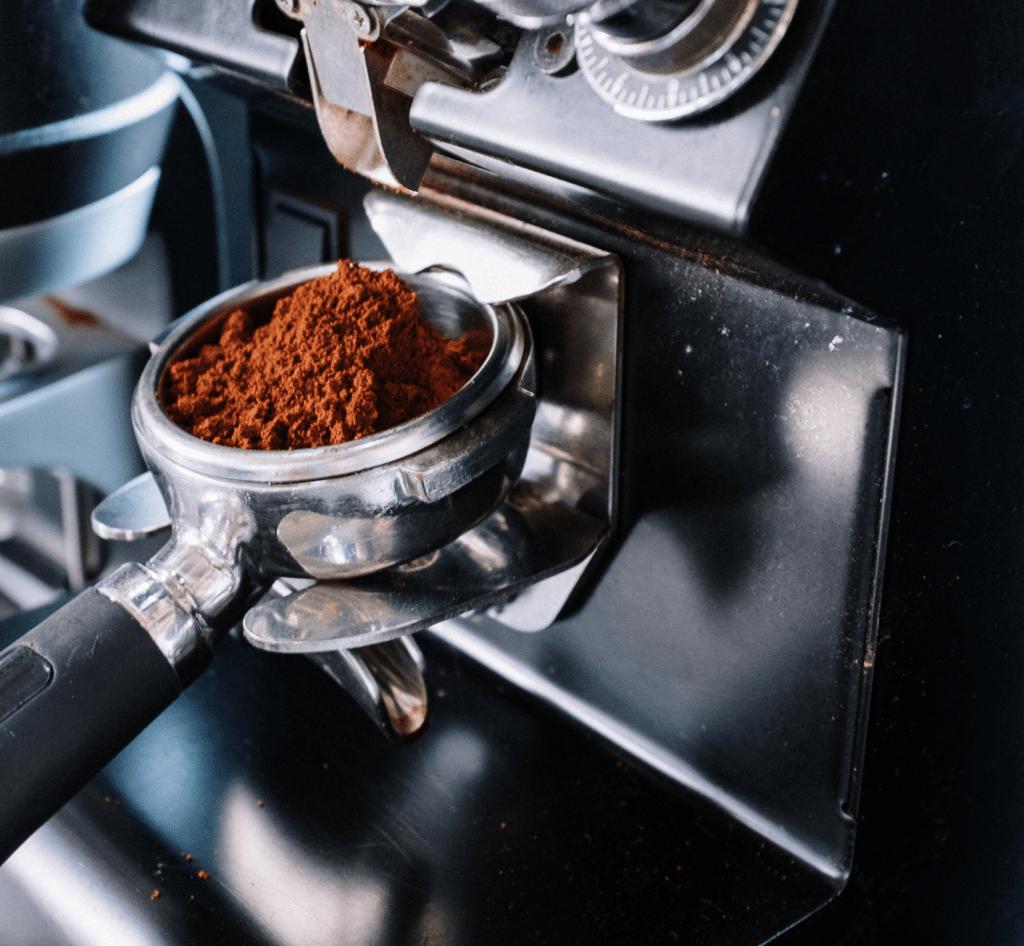 páka s mletou kávou v držáku u espresso mlýnku