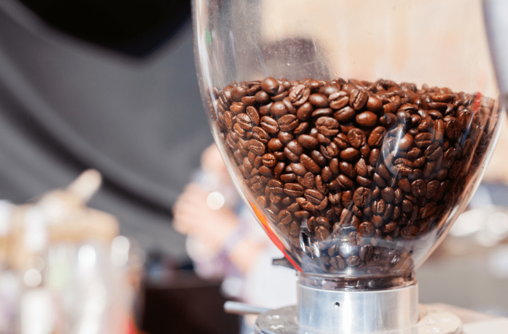 kávová zrnka v násypce u elektrického mlýnku na kávu