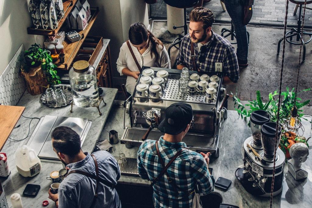 dva baristé připravují za barem kávu pro dva čekající zákazníky