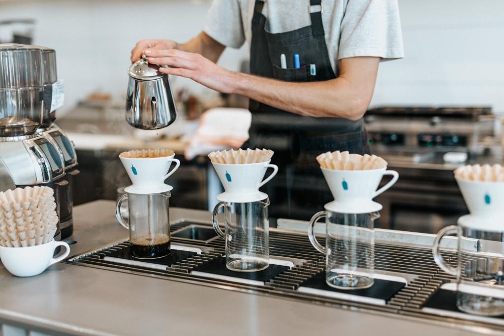 barista připravuje čtyři filtrované kávy formou přípravy v bílých keramických V60