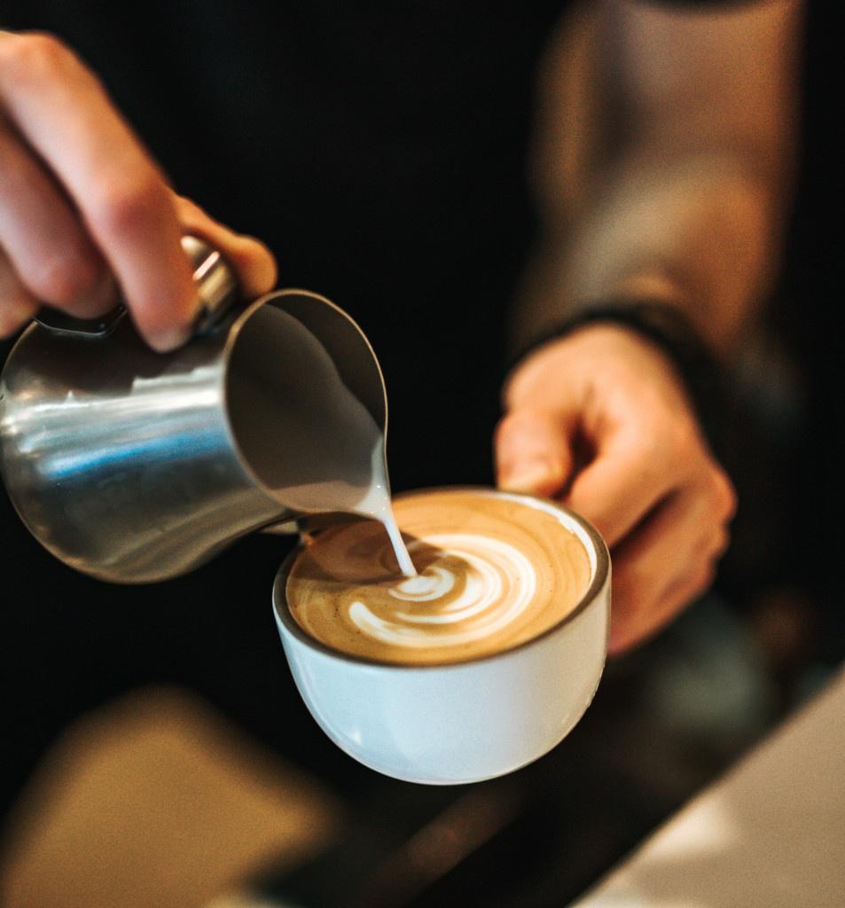 tvorba latte artu do cappuccina v bílém šálku