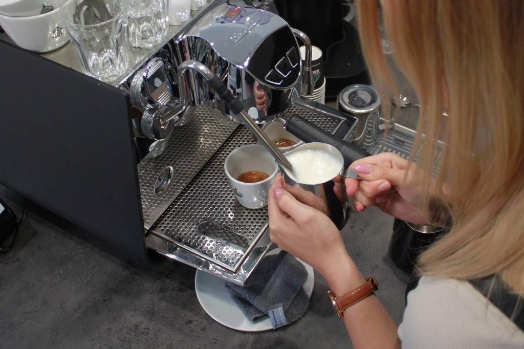 baristka šlehá mléko v baristické konvičce na trysce u kávovaru