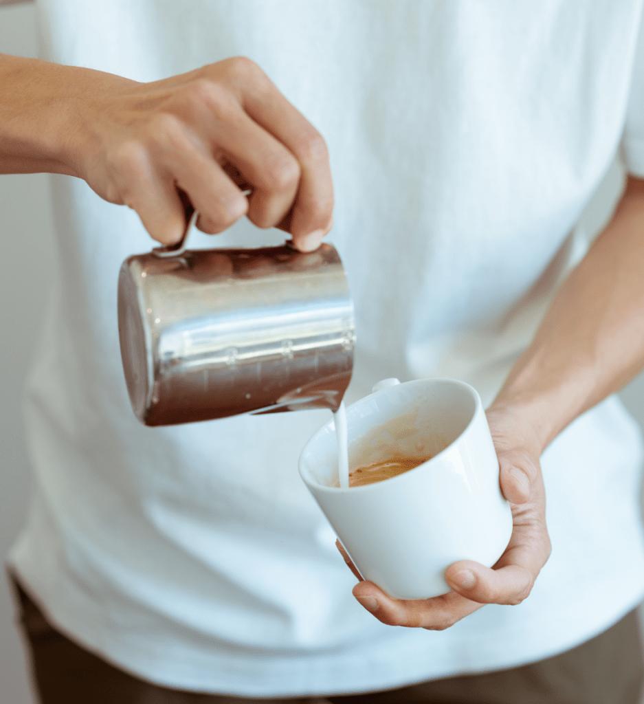 muž lije mléko z baristické konvičky do šálku