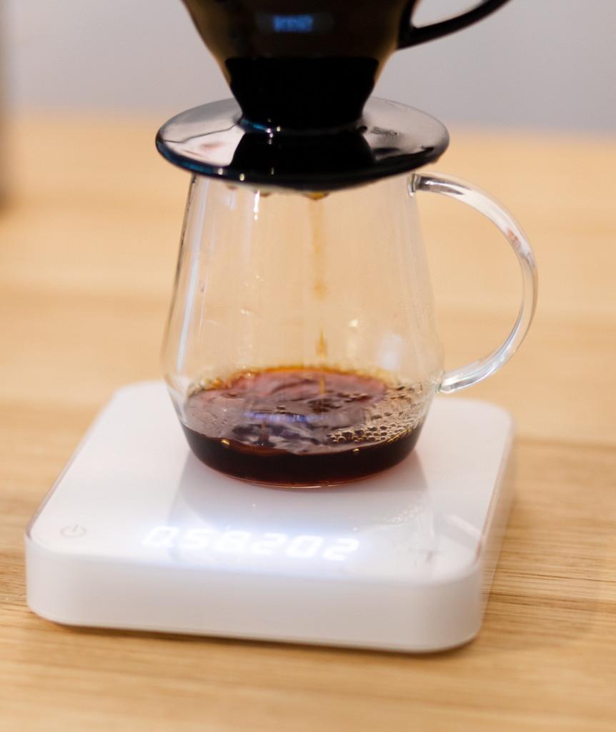 příprava filtrované kávy v černém keramickém dripperu Hario V60 na bílé baristické váze Acaia