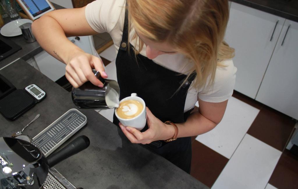 baristka vytváří tulipán v cappuccinu