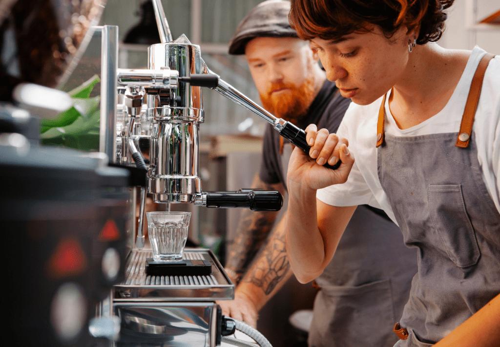 baristka stlačuje páku u ručního pákového kávovaru