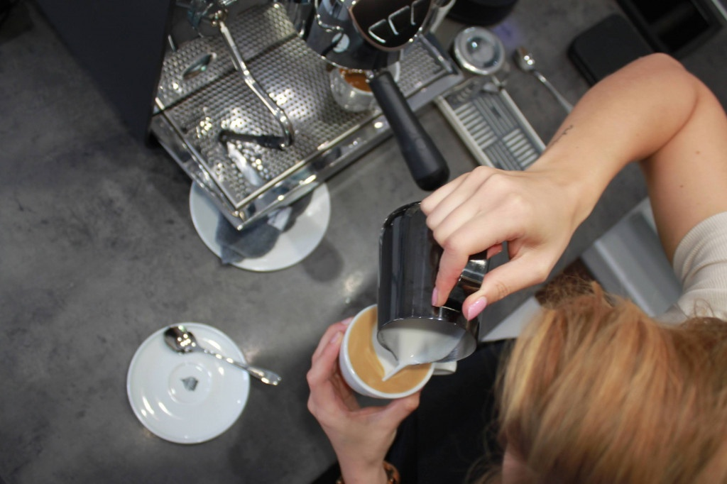 pohled shora na baristku zakončující latte art