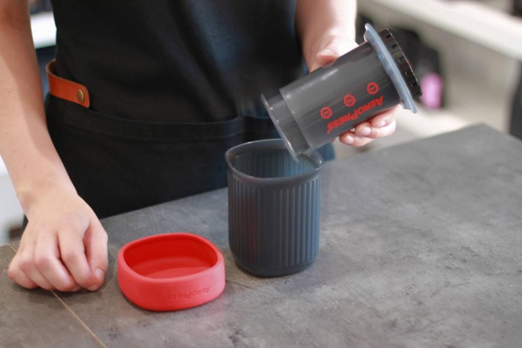 šedý cestovní nástroj na přípravu filtrované kávy AeroPress Go s červeným víčkem