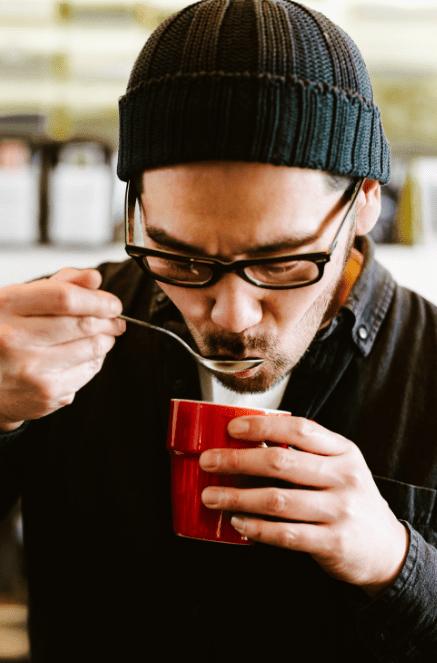 muž v čepici srkající kávu z cuppingové lžíce