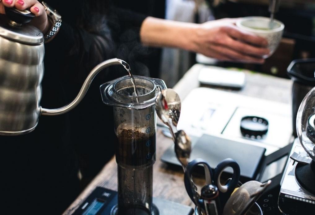 barista připravuje filtrovanou kávu v AeroPressu